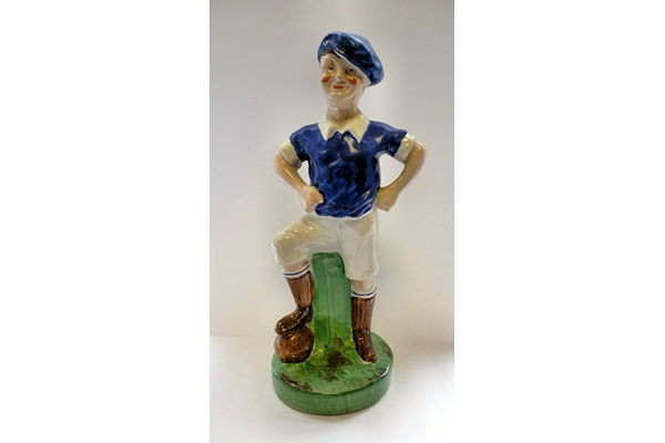 Ceramic footballer figurine. The figure was probably intended to be a Glasgow Rangers FC player with other versions of the same figure are known to have been painted in Celtic FC colours. - Late 19th/early century - 2006.193 - © McLean Museum and Art Gallery, Greenock.
