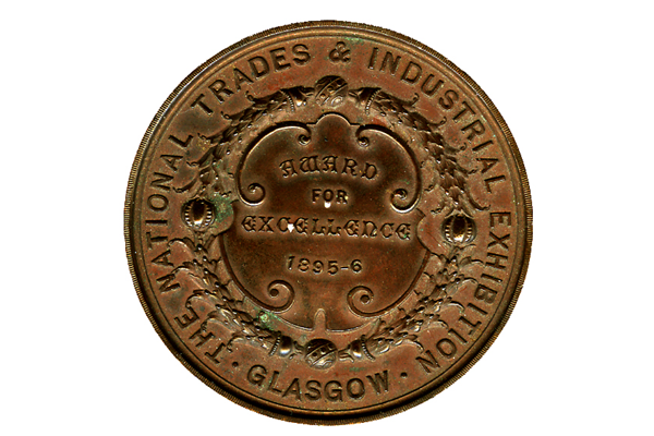 Copper medal of The National Trades & Industrial Exhibition Glasgow 1896 awarded for Excellence to Neil Campbell for the construction of a rowing cutter model. - 2007.888 - © McLean Museum and Art Gallery, Greenock