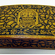 Small Mauchline ware wooden box decorated with a thistle design on all faces. In the centre of the lid is a coat of arms bearing the motto 'QUOD TIBI HOC ALTERI', motto of the Crawfurd of Cartsburn Family. - 1981.1104