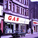 Colour transparency by Eugene Jean Méhat (1920-2000) showing a scene in Greenock during the mid 1960s. This shows a view dated 25-8-67 showing West Blackhall Street with Gas Board showroom, MacDonald Cleaners and Hector Russell shop. - 2008.72.154  - © McLean Museum and Art Gallery, Greenock.